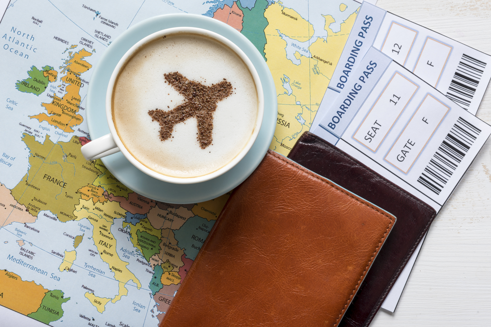 Airplane made of cinnamon in cappuccino, Passports and Europe map