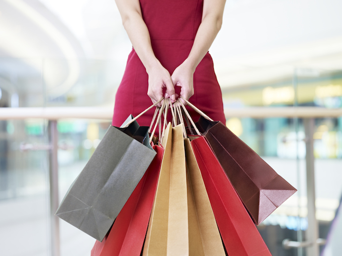 young woman carrying paper shopping bags in modern mall
